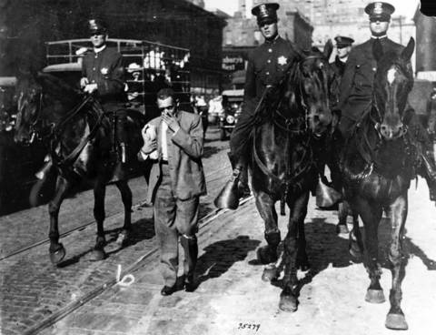"The mounted police round up ""stray"" African-American's and escort them back to a safety zone during the race riots in Chicago in 1919."