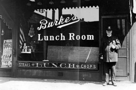 A police officer stands in front of Burke's Lunch Room in the heart of Chicago's business district. A black man was dragged out through a window and beaten to death on the sidewalk in front of the lunch room during the race riots of 1919. The hole in the window is covered up with a board. Photo dated July 30, 1919.