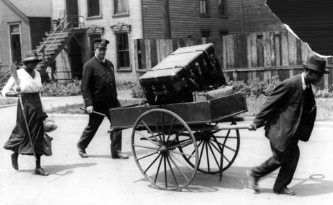 Black residents of the south side move their belongings with a hand-pulled truck to a safety zone under police protection during the Chicago race riots of 1919.