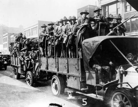 Army trucks loaded with troops are rushed to the South side of Chicago to quell the race riot of 1919.