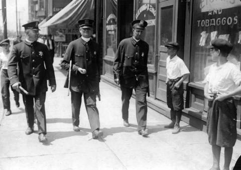 Police armed with rifles walk their beat next to the 'Black Belt' during the Chicago race riots of 1919. Photo dated July 30, 1919.