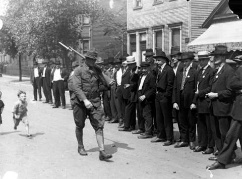 A soldier walks past a group of men during the Chicago race riots of 1919.