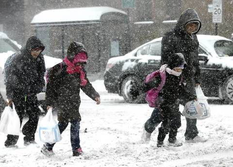 A family crosses a snow covered west Cermak Road as snow continues to fall.