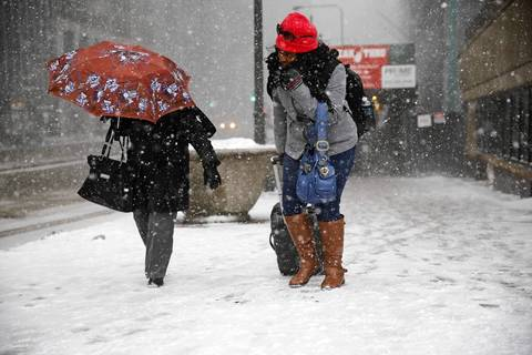 Pedestrians fight the wind as they approach East Randolph Street at North Michigan Avenue as snow and high winds hit the area.