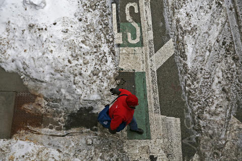 A pedestrian crosses the bicycle lane on West Kinzie Street near the Merchandise Mart in Chicago on Monday. A new snow storm is expected to bring 4-8 inches.