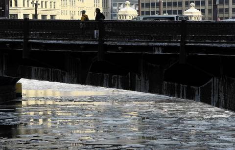Pedestrians cross the Michigan Avenue bridge above an icy river.