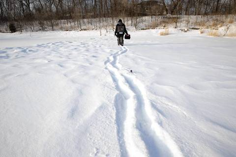 Mike McNett of Lombard, captain of the USA Ice Team, leaves a trail in the snow as he looks for a spot to ice fish on a pond at Westmore Woods in Lombard.
