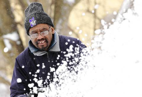 Walter Edwards, 60, blows snow from the driveway of a friend near Livingston and Eastwood Streets in Evanston.