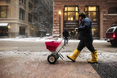 A worker uses a spreader to coat a stretch of sidewalk with salt in Chicago's Loop after an overnight snow storm covered the city.