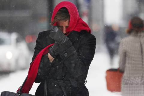 A woman braces against the blowing snow as she makes her way through Chicago's Loop.