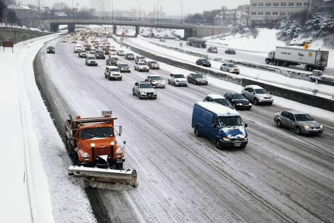City snow plows work to clear the snow-covered Kennedy Expressway in Chicago after an overnight snow storm covered the city.