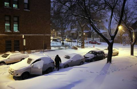 An early morning commuter scrapes snow from his car after an overnight snow storm covered the city.