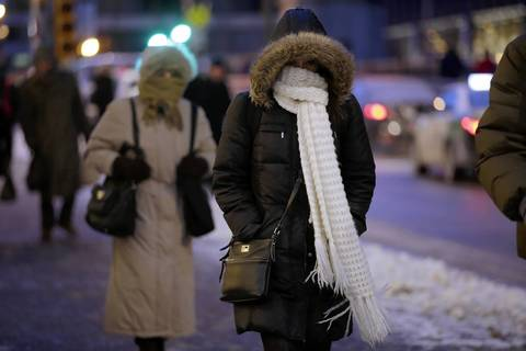 Commuters braces themselves for the cold weather as they leave Union Station on Adams Street in downtown Chicago.