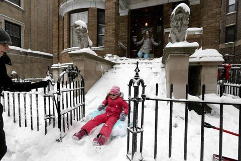Samantha O'Brien, 12, watches as her sister Sydney, 9, sleds down the sledding hill she has created out of the front steps of their north side Chicago home. The girls were asked to go shovel the steps but packed them full of snow instead.
