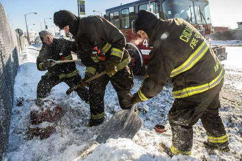 Fireman from Engine 49, Pat Galvin, left, Chris Killham and Pat Amend dig out a hydrant along Pershing Road in Chicago as daytime temperatures register -13F Chicago.