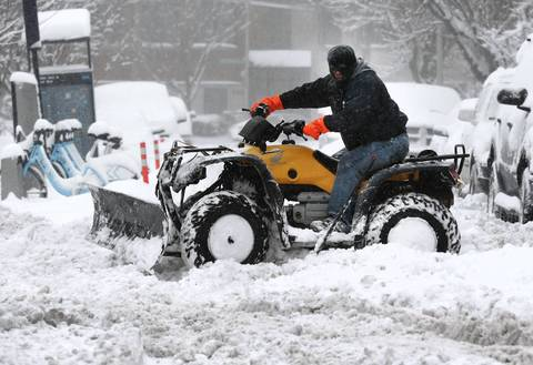 A man uses a power sport vehicle to remove snow from a sidewalk near the 1200 block of W. Race Avenue, in Chicago.