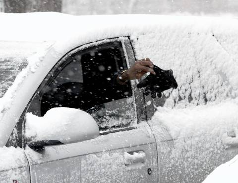 A driver in River Forest reaches out of his car window and uses a glove to clear off snow.