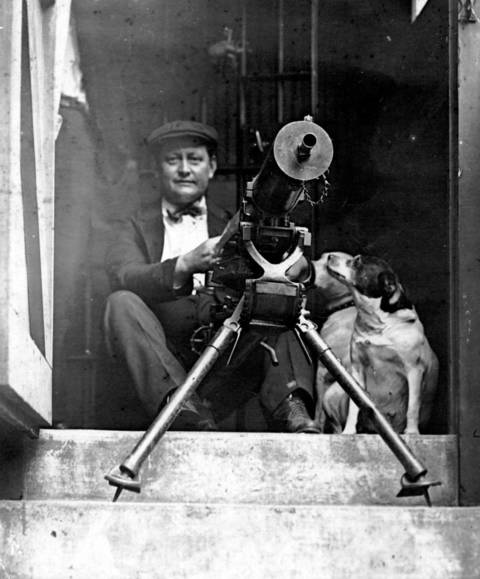 A man armed with a machine gun sits at the Cook County Jail during the 1919 Chicago race riots.