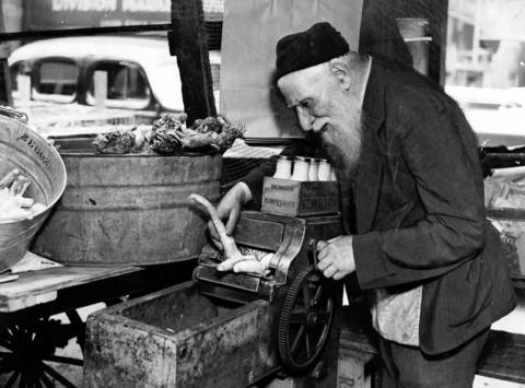 "Soroka Rayfield, 70, grinds horseradish at Maxwell Street Market in 1938. Rayfield had made a living on Maxwell Street for 20 years grinding and selling horseradish. According to the original caption, Rayfield is not worried ""about the suggestion that the Maxwell St. market be wiped out. This is his only livelihood and he may be seen any Thursday at the Ghetto market."""