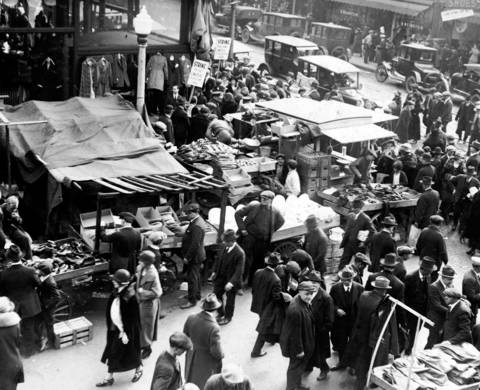A springtime crowd shops at Maxwell and Halsted Streets at the market in the early 1920s. Note the striking garment workers picketing in the background.