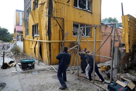 Workers try to repair the gate of a bakery damaged during a shelling in the Kievski neighborhood in northern Donetsk.