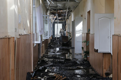 A firefighter walks among charred debris in a school which was engulfed in flames during what locals say was recent shelling by Ukrainian forces in Donetsk.