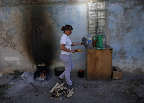 A woman prepares food in the Ukrainian city of Avdeevka near Donetsk. Fighting between the Ukrainian army and pro-Russian separatists have rendered the city without electricity and gas.