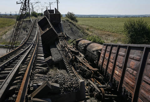 Train wagons are seen on the destroyed railway bridge which collapsed during the fighting between the Ukrainian army and pro-Russian separatists over a main road leading to the eastern Ukrainian city of Donetsk.