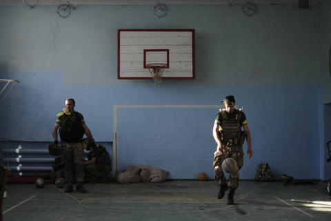 Ukrainian servicemen play basketball in a school building in the eastern Ukrainian town of Ilovaysk.