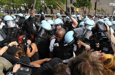The helmet of police Lieutenant Glenn Evans is knocked off in the skirmish as protesters and police clash.
