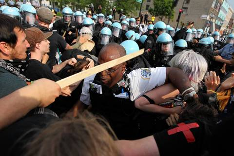 A protester whacks Lt. Evans over the head with a stick.