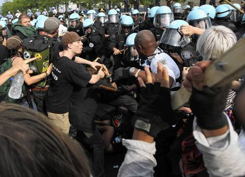 Lt. Evans begins to fall backward after being hit with the stick. A different protester draws a stick, at right.