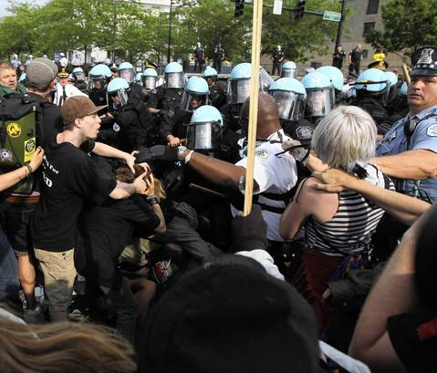 The protester swings at Lt. Evans as a fellow officer, right, steps in.