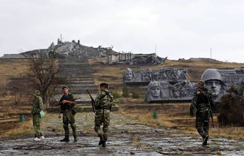 Pro-Russian separatists walk towards a destroyed war memorial at Savur-Mohyla, a hill east of the city of Donetsk, August 28.