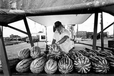 Maxwell Street watermelon man, Bob Webb, sets up his watermelon stand at Maxwell and Halsted Streets on Aug. 10, 1987. Webb said he can sell out in half a day in hot weather, but that sales have been slow lately.
