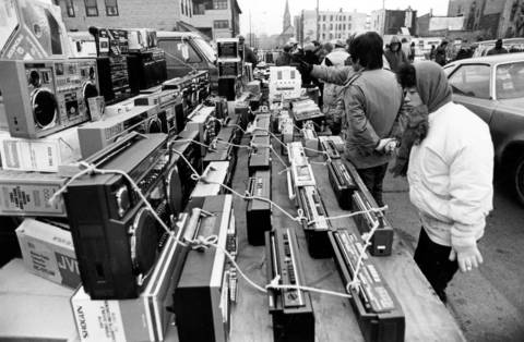 "Radios beckon to shoppers along Maxwell Street on Nov. 30, 1986. ""You have to know what you're looking for,"" says a frequent visitor to the area. ""That's the secret down here."""