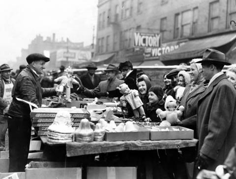 A Maxwell Street vendor tries to entice late Christmas shoppers with ornaments and dolls on Dec. 24, 1944.