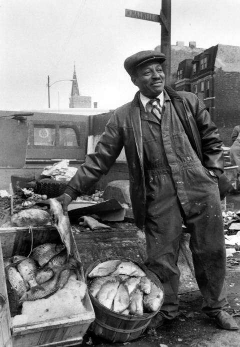 A fishmonger tries to catch the attention of shoppers on a cold Sunday at Maxwell Street Market on Feb. 3, 1974.