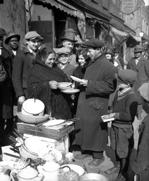 Joe Kaplan sells dishes to Mrs. Freida Sawyer at Maxwell and Peoria Streets, circa April 1927.