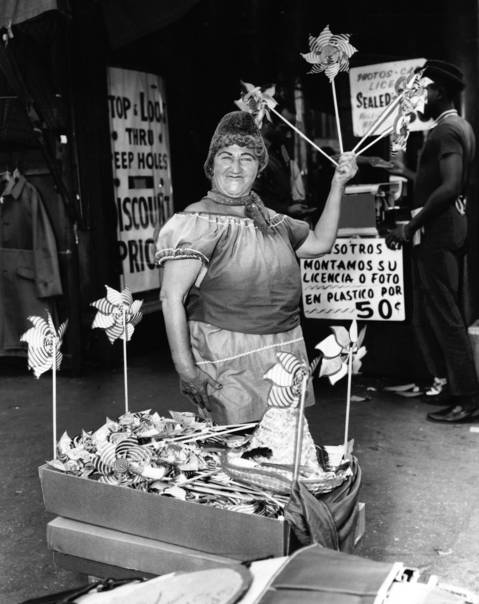 "Maxwell Street had its share of characters, including Margo, who sold pinwheels at the corner of Maxwell and Halsted Streets in August 1963. The original caption said this: ""This is our world, old but good. We won't be wanted when the new University of Illinois is built,"" said Margo. About six blocks of the market was eliminated because of expressway construction."