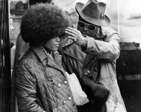 A seller adjusts a wig on a tempted buyer at Maxwell Street market on Feb. 3, 1974.