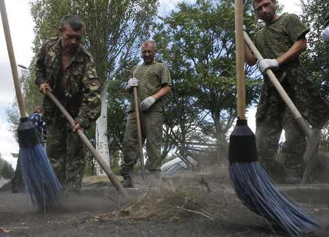 Prisoners of war, who are Ukrainian servicemen captured by pro-Russian separatists, clean a street in the Donetsk region, August 29.