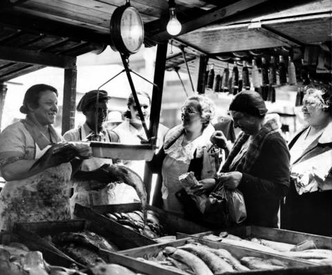 Sarah Neiman, from left, and George Cohen weigh fish and chat with customers Bertha Bluestein, Sophie Paletz and Olive Greenburg at Maxwell Street Market, circa May 18, 1934