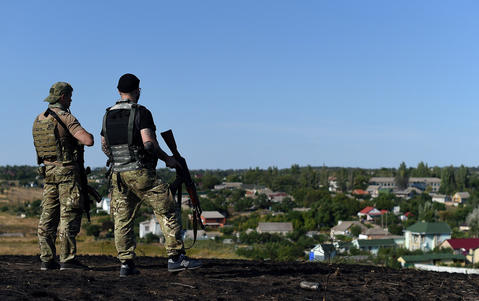 Ukrainian loyalist fighters from the Azov Battalion stand guard on a hill on the outskirts of Mariupol on Aug. 30.