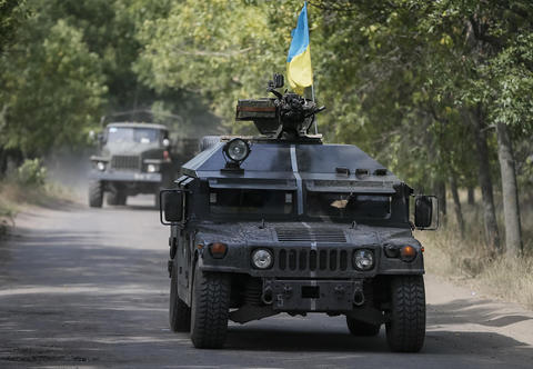 Ukrainian military members ride in an armoured vehicle in Kramatorsk on Sept. 1.