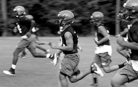 Woodside High football team warms up for the first day of pre-season practice Thursday evening.