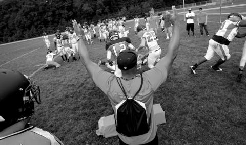 A Tabb High coach signals a touchdown during 4-on-4 drills at a pre-season practice.