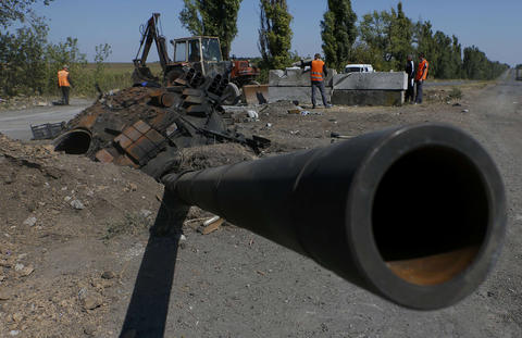 A turret with a gun from a Ukrainian army tank is pictured Sept. 2 at the site of a destroyed Ukrainian checkpoint as road workers clear debris outside the town of Olenivka near Donetsk in eastern Ukraine.