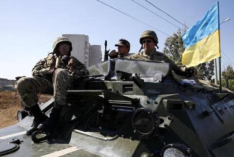 "Soldiers of the Ukrainian self-defence battalion ""Azov"" sit in an armoured personnel carrier at a checkpoint in the southern coastal town of Mariupol."