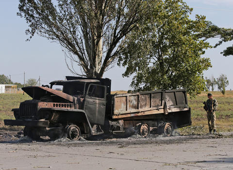 A Ukrainan soldier stands guard at a still smoldering military truck on a road in the eastern Ukrainian city of Mariupol on Sept. 7.